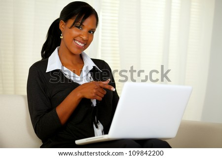 Portrait of a woman on black suit pointing to laptop screen while sitting on sofa at home indoor and looking at you - stock photo