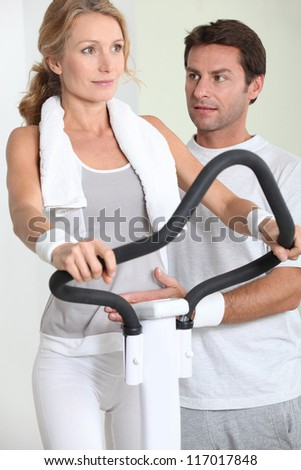 portrait of a woman on exercise bike with coach