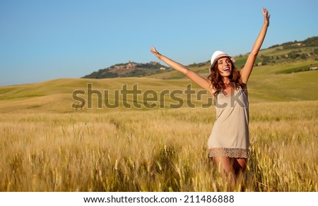 Portrait of a woman on golden cereal field in summer  - stock photo