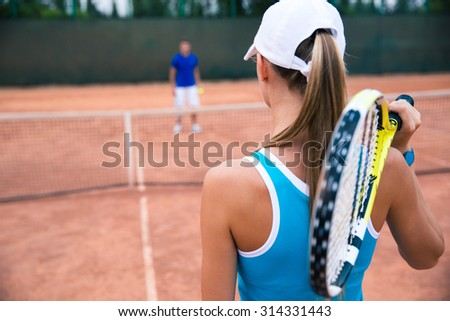 Portrait of a woman playing in tennis with man outdoors