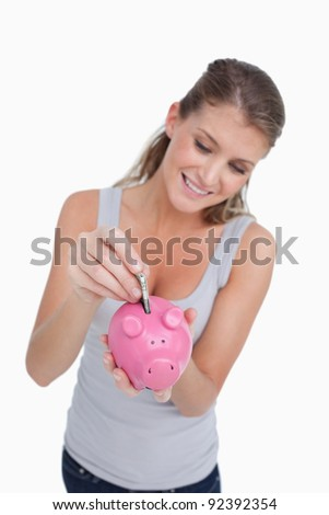 Portrait of a woman putting a note in a piggy bank against a white background - stock photo