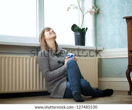Portrait of a woman relaxing at home with a cup of tea