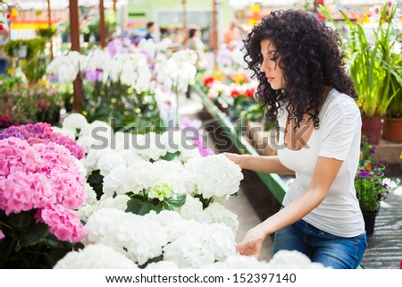 Portrait of a woman shopping in a greenhouse - stock photo