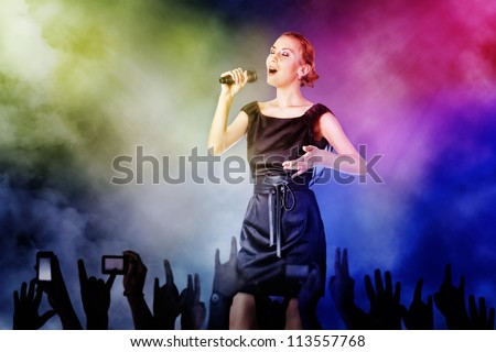Portrait of a woman singing for her fans on a concert - stock photo