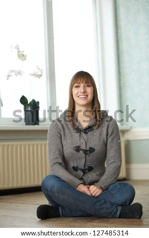 Portrait of a woman sitting and smiling - stock photo