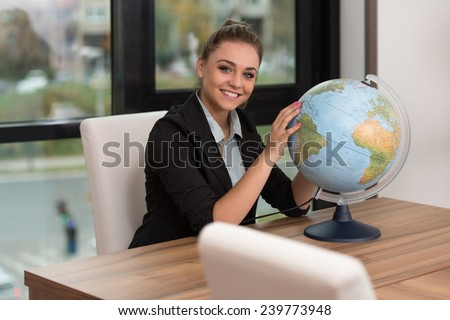 Portrait Of A Woman Sitting By Her Desk And Holding A Globe Model - stock photo
