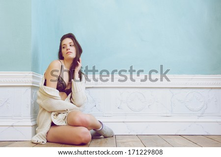 Portrait of a woman sitting on floor in underwear and sweater