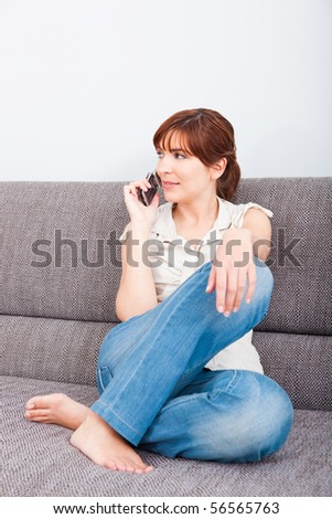 Portrait of a woman sitting on sofa, talking on phone