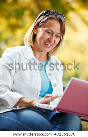 Portrait of a woman sitting with a laptop on her lap