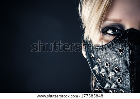 portrait of a woman slave in a mask with spikes - stock photo