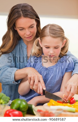 Portrait of a woman slicing pepper with her daughter in a kitchen
