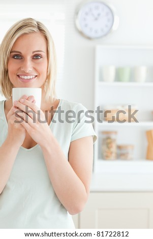 Portrait of a woman taking in smell of coffee looking into the camera in the kitchen