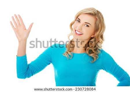 Portrait of a woman waving to the camera. - stock photo
