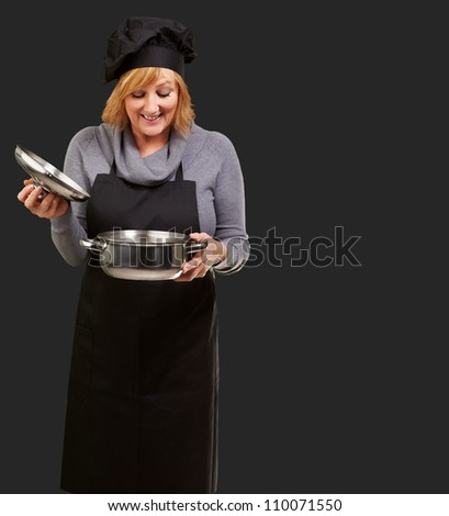 Portrait Of A Woman While Cooking Food On Black Background