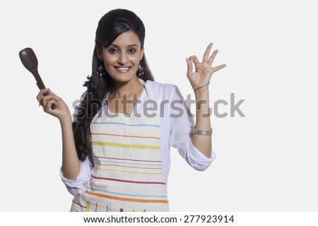 Portrait of a woman with a cooking utensil giving ok sign - stock photo