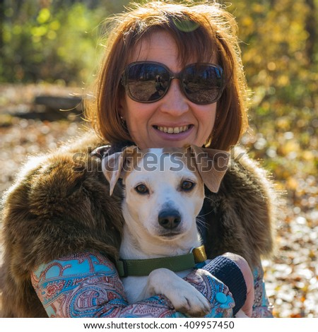 portrait of a woman with a dog on holiday in the autumn park,  age of 40 years