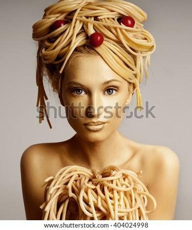 Portrait of a woman with a lot of pasta on head. Pasta with tomatoes. Girl with food hair style. Body painting.