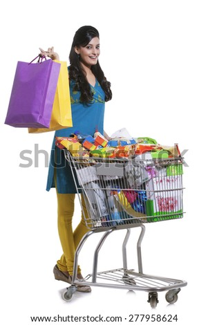 Portrait of a woman with a shopping cart and shopping bags - stock photo