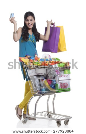 Portrait of a woman with a shopping cart , shopping bags and credit card - stock photo