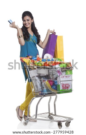 Portrait of a woman with a shopping cart , shopping bags and credit card