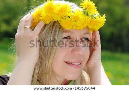 portrait of a  woman with a wreath from dandelions on a head
