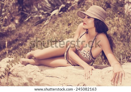 Portrait of a woman with beautiful body wearing bikini and sun hat