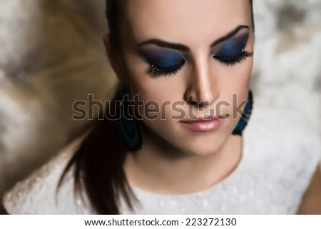 Portrait of a woman with blue smokey eyes make-up and bijou - stock photo