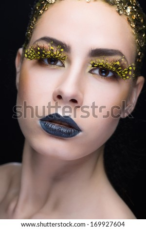 Portrait of a woman with bright makeup on black background