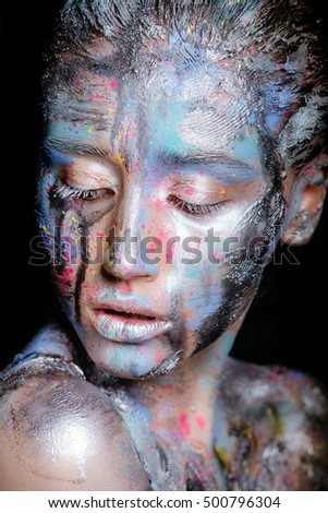 Portrait of a woman with colorful paint brushstroken on face. Bright blue eyes. Advertising Space