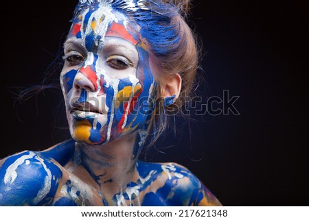 Portrait of a woman with face art.  who is posing covered with blue, red paint - stock photo