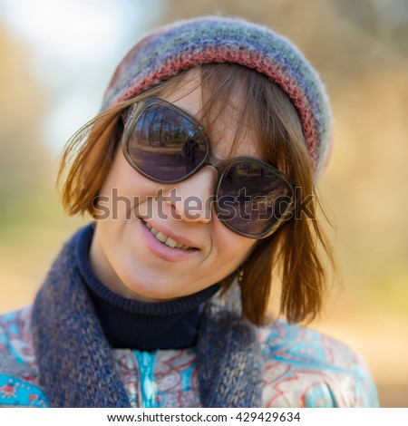 portrait of a woman with glasses in autumn park, the age of forty years