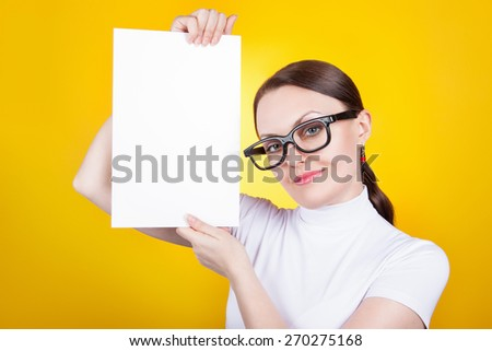 portrait of a woman with glasses on a yellow background. Business woman holding a poster