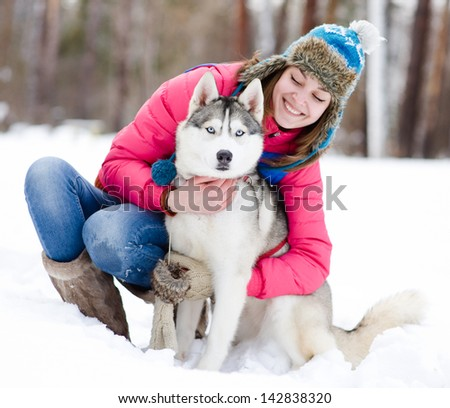 Portrait of a woman with her beautiful dog sitting outdoors - stock photo