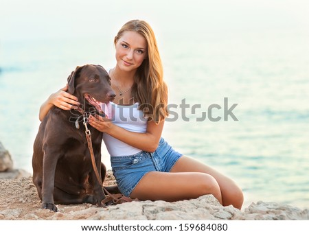 Portrait of a woman with her beautiful dog sitting outdoors. - stock photo