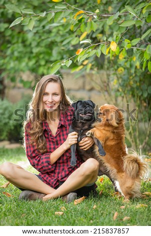 Portrait of a woman with her beautiful dogs relaxing outdoors
