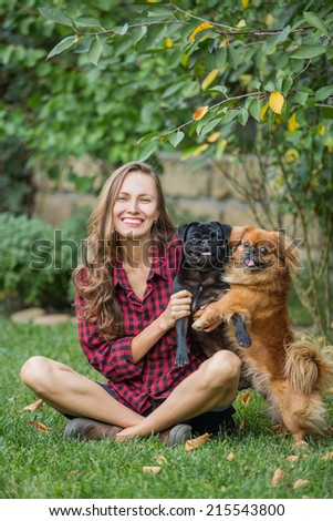 Portrait of a woman with her beautiful dogs relaxing outdoors. soft daylight,  focus on woman - stock photo