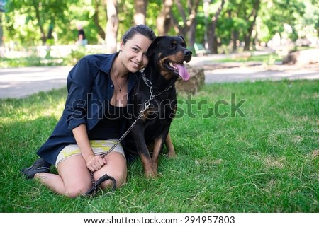 Portrait of a woman with her beautiful rottweiler lying outdoors