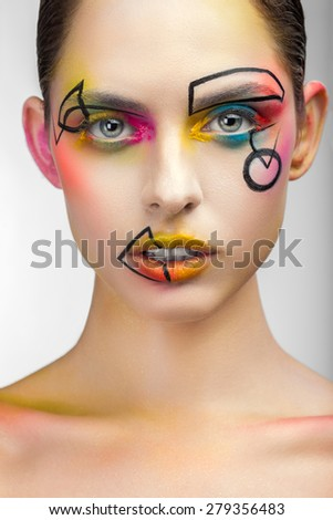 Portrait of a woman with make-up and drawings on his face close up