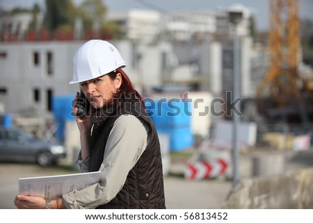 Portrait of a woman with safety helmet and mobile phone - stock photo