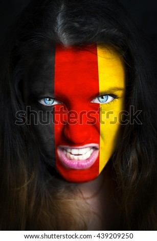 Portrait of a woman with the flag of the Germany painted on her face.  - stock photo
