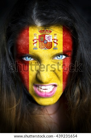 Portrait of a woman with the flag of the Spain painted on her face. - stock photo