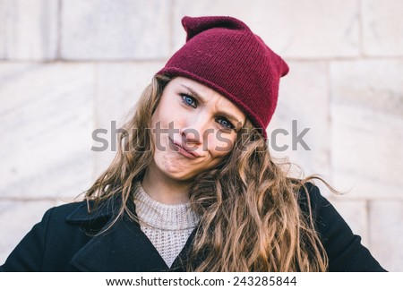 portrait of a woman with winter clothes and funny expression - stock photo