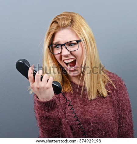 Portrait of a woman yelling at headhone against gray background - stock photo