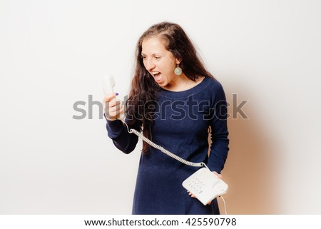 Portrait of a woman yelling at phone - stock photo