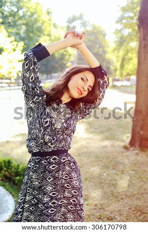 Portrait of a Woman. Young girl in the park. Dance. Femininity and tenderness. Enjoy, relax. Rest in the park. Dark blue dress with a pattern. Dancing girl. Elegant young woman. - stock photo