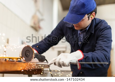 Portrait of a worker grinding a metal plate - stock photo