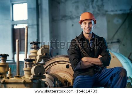 Portrait of a worker in the helmet near the turbine.