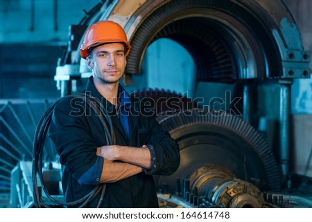 Portrait of a worker in the helmet near the turbine.