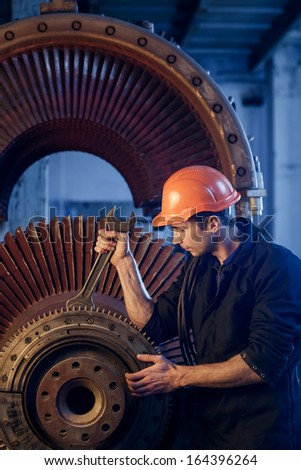 Portrait of a worker repairs powerful steam turbine. - stock photo