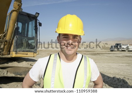 Portrait of a worker wearing hardhat in front of a crane at construction site - stock photo